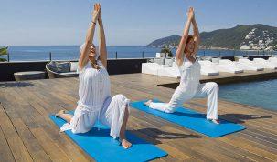 Realizando yoga en las turquesas aguas de Ibza