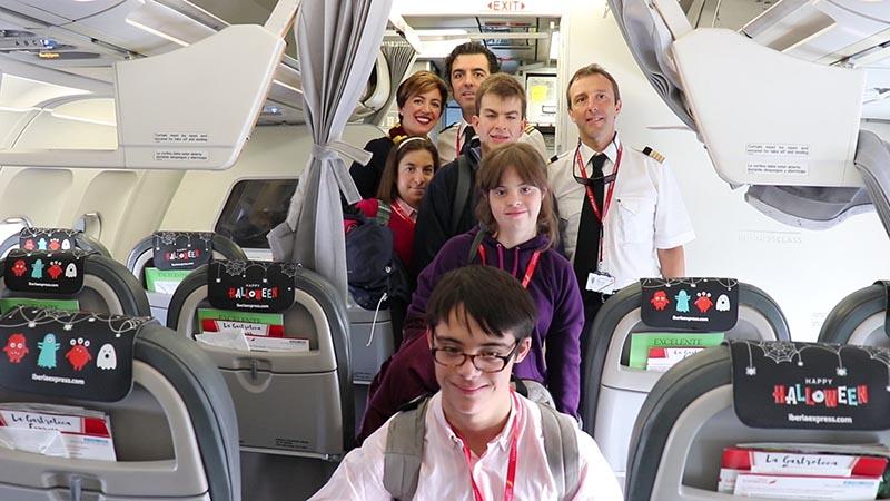 Foto de familia de algunos de los jovenes y la tripulación del Avión