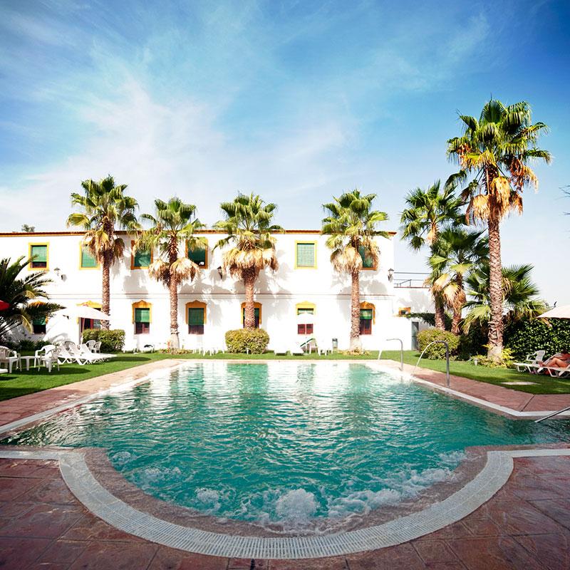 Fachada del balneario El Raposo y la piscina